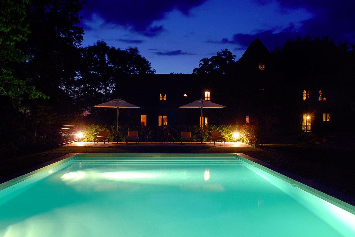 la piscine sur fond du manoir et ses chambres d'hotes de charme