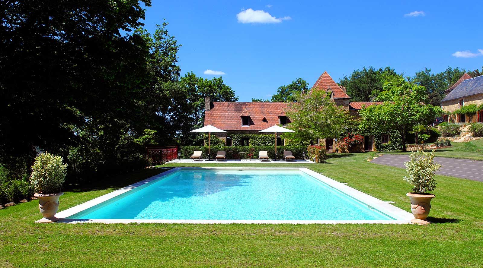 une piscine dans un manoir avec deux chambres d'hotes haut de gamme